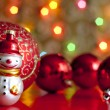 Snowman and baubles against blurred colorful background — Stock Photo