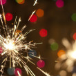 Sparkler and colorful bokeh christmas new year background — Foto de Stock