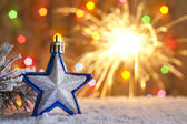 Christmas star on snow and blurred background with sparklers — Stock Photo