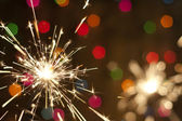 Sparkler and colorful bokeh christmas new year background — Stock Photo