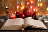 Christmas and bible with blurred candles light background — Photo
