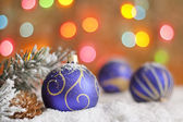 Christmas baubles on snow against blurred colorful background — Stock Photo