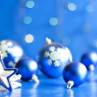 Christmas star closeup and baubles on blue blurred background — Stock Photo