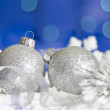 Christmas branch of tree ribbon silver baubles and snow on blue background — Stock Photo