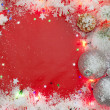 Christmas lights border with baubles and snow on red background — Stock Photo