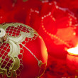 Stock Photo: Christmas red bauble and candle on blurred background