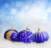 Christmas blue baubles on abstract blurred background closeup — Stock Photo