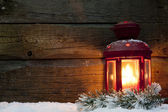 Christmas lantern light in night on snow and wooden boards — Stock fotografie