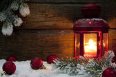 Christmas lantern in night on snow with baubles background — Stock Photo