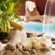 Spa concept with stones orchids waterfall in pool and sunbed — Stock Photo