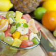 Fresh fruits salad in bowl in kitchen closeup — Stock Photo #16262253