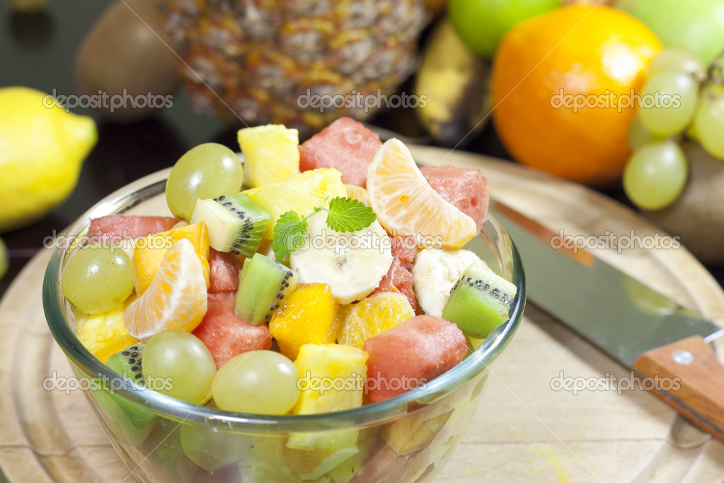 Fresh fruits salad in bowl in kitchen closeup — Stock Photo #16262277