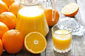 Orange juice with squeezer and jug on wooden boards — Stock Photo