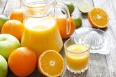 Orange juice with lime grapefruit and squeezer on wooden boards — Stock Photo