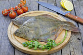 Flounder raw fish on cutting board in kitchen — Stock Photo