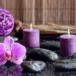 Purple orchid candles and zen stones spa concept still life — Stock Photo