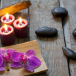 Spa stones orchids and candle on wooden boards — Stock Photo #18246501