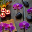 Spa stones orchids and candle on wooden boards — Stock Photo #18246525