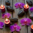 Spa stones orchids and candle on wooden boards — Stock Photo