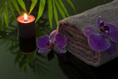 Orchid and towel with candle in night spa concept — Stock Photo