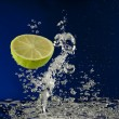 Fruit lime splash in water with bubbles against blue background — Stock Photo