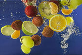 Fruits splash in water with bubbles against blue background — Zdjęcie stockowe