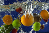 Fruits splash in water with bubbles against blue background — Stock Photo