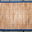 Bamboo mat on vintage wooden boards food background concept — Stock Photo