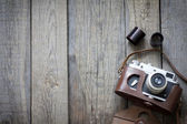 Old retro camera on vintage wooden boards abstract background — Stock Photo