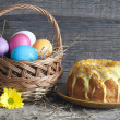 Easter eggs in the basket and cake on vintage wooden table — Stock Photo
