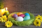 Huevos de pascua en nido verde sobre tablones de madera vintage — Foto de Stock