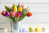 Spring easter tulips in bucket on white vintage planks — Stock Photo