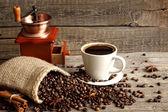 šálek kávy a mlýnek na vinobraní zátiší na prkna — Stock fotografie