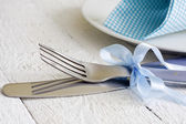 Cutlery and ribbon on old vintage wooden table closeup — Stock Photo