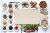 Spices and dried vegetables with cutting board on white planks — Stock Photo