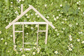 Wooden home in spring green grass ecological building concept — Stock Photo