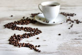 Cup of coffee with beans on retro vintage white planks concept — Stockfoto