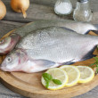Bream raw fish on cutting board in the kitchen with spices — Stock Photo