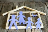 Family and home concept, paper silhouettes on wooden boards — Stock Photo