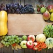 Foto Stock: Autumn fruits and vegetables and empty cutting board