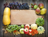 Autumn fruits and vegetables and empty cutting board — Stock Photo
