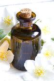 Jasmine aromatherapy oil on white planks with flowers — Stock Photo