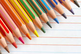Colorful pencils crayons on white paper abstract background — Stockfoto