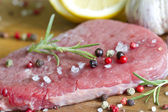 Raw beef steak on cutting board with spices — Stock Photo