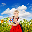 Bavarian girl in tracht dress dirndl in sunflower field — Stock Photo #13371804