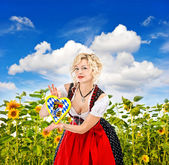 Bavarian girl in tracht dress dirndl in sunflower field — Stock Photo