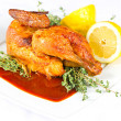 Grilled chicken on a white plate with spicy sauce and lemon - Stock fotografie