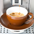 Coffee maker pouring fresh coffee in a cup — Stock Photo
