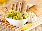 Olives and garlic with tasty Italian and grain bread — Stock Photo