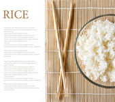 Bowl of white steamed rice with chopsticks on bamboo mat — Stock Photo